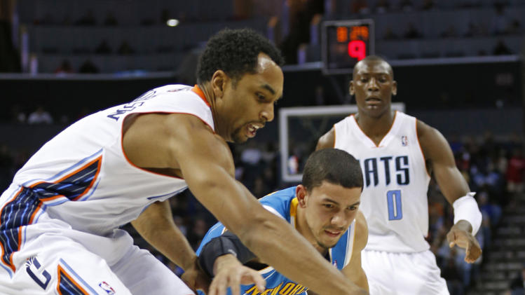Charlotte Bobcats' Gerald Henderson, left, and New Orleans Hornets' Austin Rivers, right, chase a loose ball during the first half of an NBA basketball game in Charlotte, N.C., Saturday, Dec. 29, 2012. Charlotte Bobcats' Bismack Biyombo (0) looks on in background. (AP Photo/Chuck Burton)