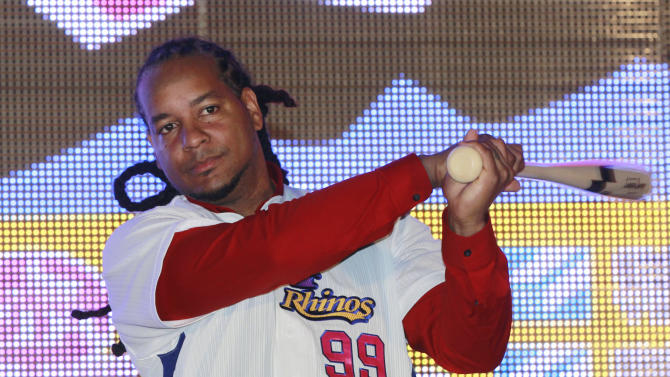 Former MLB star Manny Ramirez poses for media with an honorary baseball bat and new team jersey after signing a short-term contract to play on the EDA Rhinos in Taiwan's professional baseball league in Kaohsiung, Taiwan, Tuesday, March 12, 2013. The EDA Rhinos say Ramirez will earn $25,000 a month to appear with the team during this year's March-November season. (AP Photo/Wally Santana)