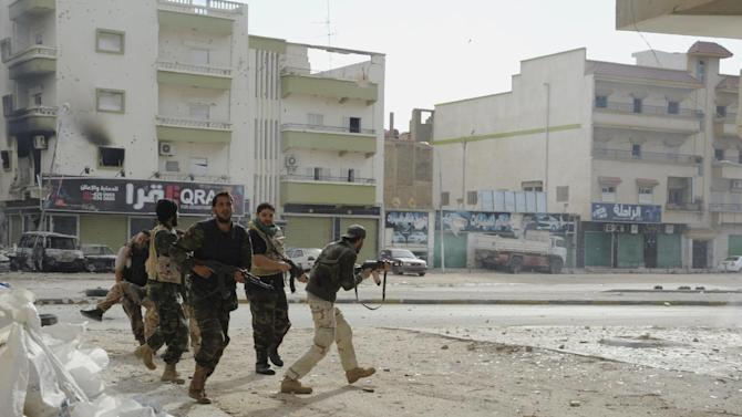 Libyan military soldiers run to take cover during clashes with Islamic extremist militias in Benghazi, Libya, Thursday, Oct. 30, 2014. Government troops entered central Benghazi Wednesday after nearly 10 days of fighting Islamic extremist militias, a military spokesman said, in violence that killed dozens of people and forced hundreds of families to flee. (AP Photo/Mohammed el-Sheikhy)