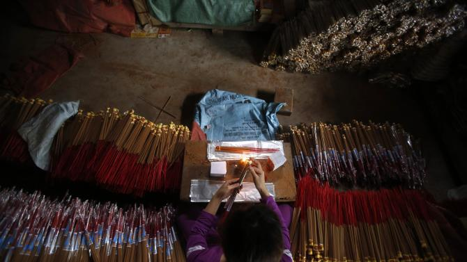 A labourer packs incense in preparation for Tet, traditional Vietnamese lunar new year, in Hong Chau village, outside Hanoi