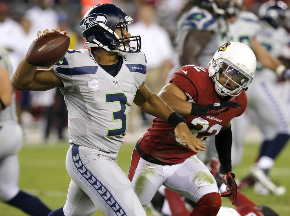 Seattle Seahawks quarterback Russell Wilson (3) scrambles as Arizona Cardinals free safety Tyrann Mathieu defends during the first half of an NFL football game, Thursday, Oct. 17, 2013, in Glendale, Ariz. (AP Photo/Ross D. Franklin)