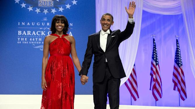 President Barack Obama and first lady Michelle Obama arrive to dance together at an Inaugural Ball, Monday, Jan. 21, 2013, at the Washington Convention Center in Washington, during the 57th Presidential Inauguration. (AP Photo/Carolyn Kaster)