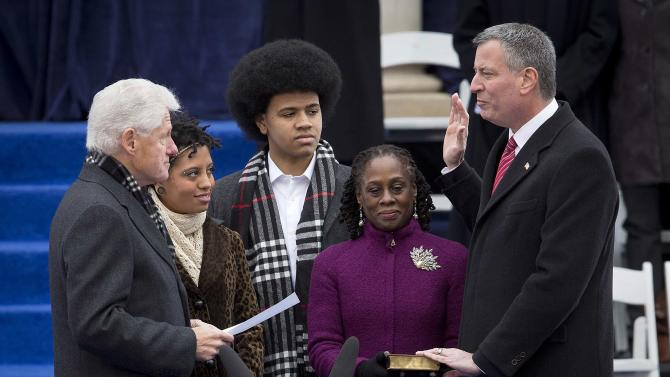 Mayor of New York Bill de Blasio is sworn in by former President Bill Clinton at City Hall in New York