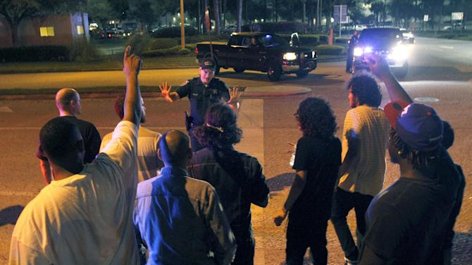A police officer tries to control a group of people trying to get to their vehicles in a parking lot at The Florida Mall in Orlando, Fla. late Thursday, Feb. 23, 2012 after more than 100 sheriff's deputies in riot gear broke up an out-of-control crowd waiting to buy a new Nike basketball shoe at one of the stores. Authorities say there were no injuries or arrests outside the Florida Mall late Thursday. The crowd began getting unruly as hundreds packed the parking lot, waiting to buy the $220, limited-edition shoe that was timed to be released during the NBA All-Star Game in Orlando. (AP Photo/Reinhold Matay)