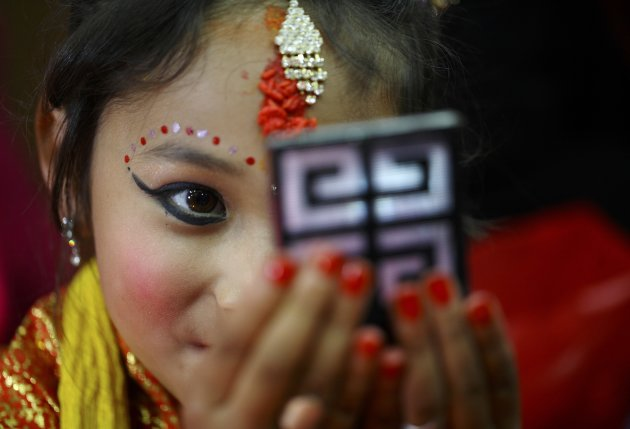 An adorned Newar girl looks at herself in the mirror during an Ihi ceremony in Kathmandu