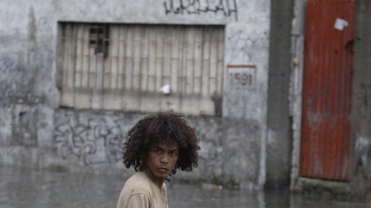 CORRECTS NAME OF THE TYPHOON - A Filipino man wades through flooded streets brought by typhoon Muifa in Manila, Philippines on Tuesday Aug. 2, 2011. Muifa continues to blow away from the northern Philippines after killing at least 4 people even though it did not make landfall. (AP Photo/Aaron Favila)