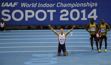 Kilty of Britain celebrates victory next to Jamaicans Carter and Roach in the men's 60 metres final at the world indoor athletics championships at the ERGO Arena in Sopot