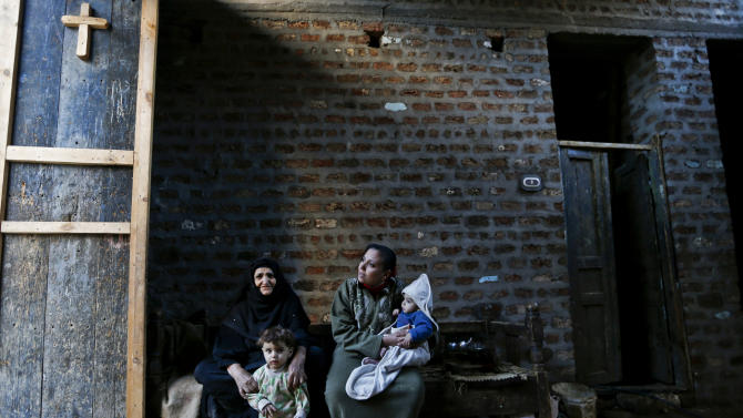 In this Tuesday, Dec. 18, 2012 photo, women sit with their children in their house in the village of El-Aziyah near the city of Assiut, southern Egypt. After a campaign of intimidation by Islamists, most Christians in this southern Egyptian province were too afraid to participate in last week's referendum on an Islamist-drafted constitution they desperately oppose, residents say. Some of the few who dared try to reach polls were pelted by stones. The disenfranchising hikes Christians' worries over their future under Egypt's empowered Islamists, but some young members of the community are starting to push back. (AP Photo/Petr David Josek)