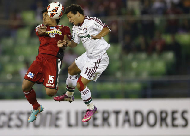 Otero of Venezuela's Caracas FC challenges Wellington of Brazil's Fluminense during their Copa Libertadores soccer match in Caracas