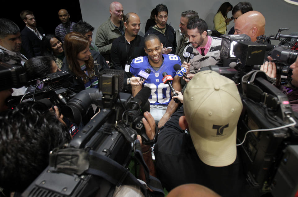 New York Giants' Victor Cruz smiles while surrounded by reporters during a presentation in New York, Tuesday, April 3, 2012. The NFL and Nike showed off the new gear in grand style with a gridiron-themed fashion show at a Brooklyn film studio. (AP Photo/Seth Wenig)