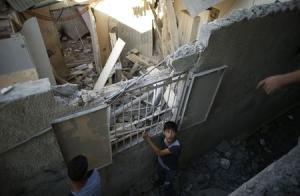 Palestinian boy stands outside a house that witnesses said was destroyed during an Israeli air strike in the northern of Gaza Strip