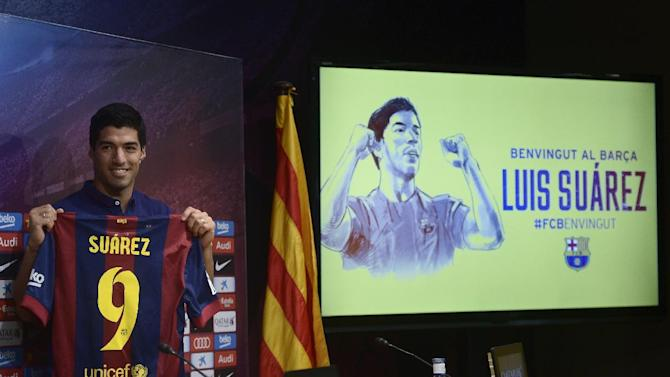 FC Barcelona's Luis Suarez, from Uruguay, holds his new shirt during a press conference of his presentation at the Camp Nou in Barcelona, Spain, Tuesday, Aug. 19, 2014. Barcelona unveiled Suarez on Tuesday, an event delayed for over five weeks since his transfer from Liverpool due to his latest suspension for biting an opponent at the World Cup