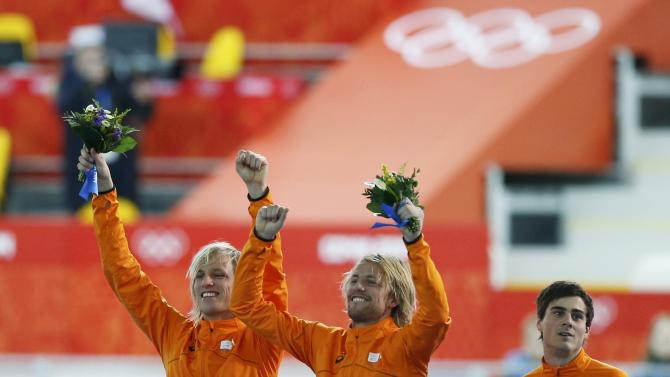 Winner Mulder, twin brother Mulder, and their compatriot Smeekens celebrate during the flower ceremony for the men's 500 metres speed skating race at the Adler Arena during the 2014 Sochi Winter Olympics