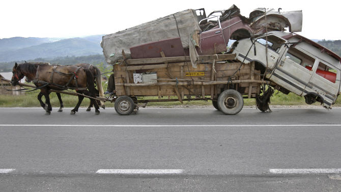 FILE - In this Sept. 8, 2010 file photo,  shows a horse pulled cart,  loaded with scrap metal on a road near Costesti, Romania. Bedraggled horses and rickety carts were once a common sight even in the center of Bucharest with owners sometimes whipping the animals until they collapsed. But as part of an effort to modernize the country after it joined the European Union in 2007, Romania banned horses from cities, making them an unjustified burden for many owners. In the countryside, peasants have a more pragmatic relationship with their animals, and look after them rather like an owner services a car. But with costs between euros 100 ($135) and euros 150 ($200) to keep a horse every month, up to 40 percent of the average national salary,  it can be far too expensive for subsistence farmers to afford them. (AP Photo/Vadim Ghirda, File)