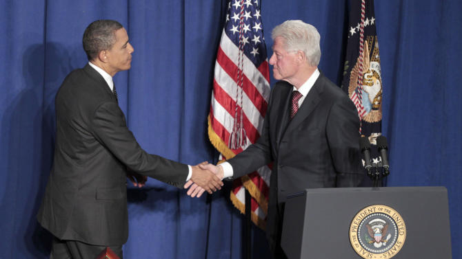 President Barack Obama, left, shakes hands with former President Bill Clinton, right, at the dedication of the Ronald H. Brown United States Mission to the United Nations Building in New York Tuesday, March 29, 2011. (AP Photo/Pablo Martinez Monsivais)