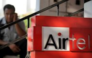 An Indian man talks on his mobile phone next to a Bharti Airtel sign in New Delhi, 2009. India&#39;s leading mobile phone firm by subscribers, Bharti Airtel, reported a worse-than-expected 28 percent dive in quarterly net profit, hit by debt charges and foreign exchange losses