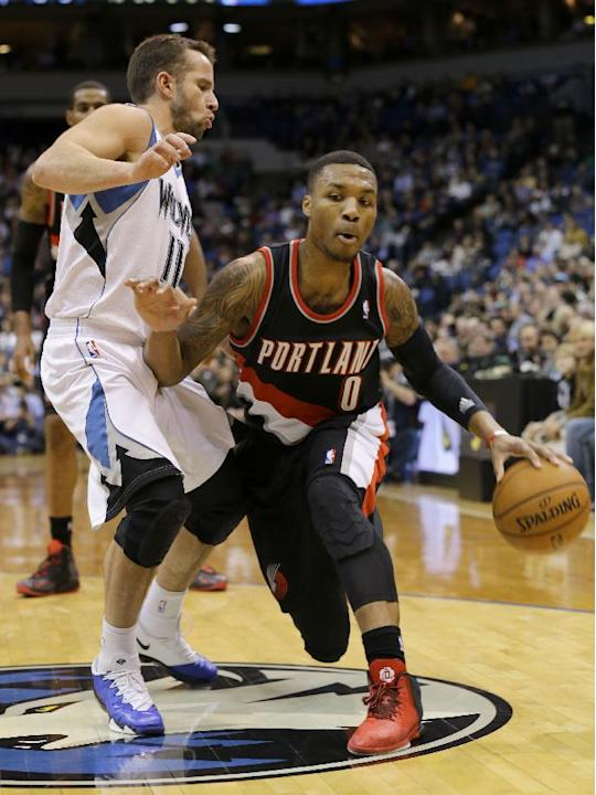 Portland Trail Blazers guard Damian Lillard (0) drives against Minnesota Timberwolves guard J.J. Barea (11), of Puerto Rico, during the second quarter of an NBA basketball game in Minneapolis, Wednesd
