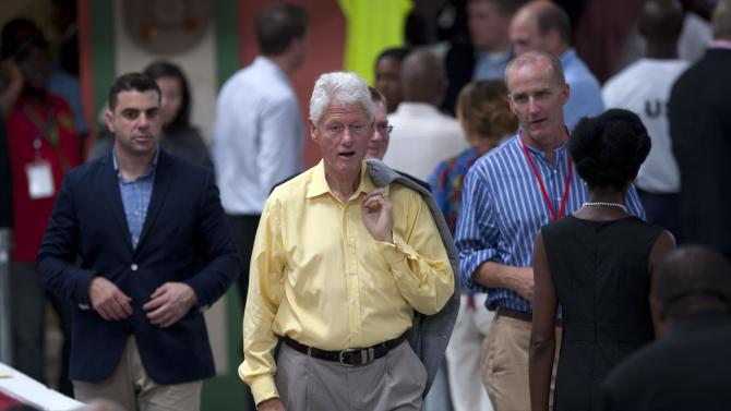 Former President Bill Clinton, center, arrives to attend the inauguration of the Caracol Haiti Industrial Park on the outskirts of Cap Hatien, Haiti, Monday, Oct. 22,  2012. Secretary of State Hillary Rodham Clinton encouraged foreigners to invest in Haiti as she and her husband Bill led a star-studded delegation gathered Monday to inaugurate the new industrial park at the center of U.S. efforts to help the country rebuild after the 2010 earthquake. (AP Photo/Dieu Nalio Chery)