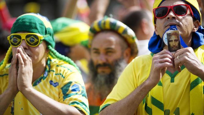 Fans of Brazil pray before a live broadcast of the World Cup round of 16 soccer match between Brazil and Chile, inside the FIFA Fan Fest area in Sao Paulo, Brazil, Saturday, June 28, 2014. (AP Photo/Rodrigo Abd)