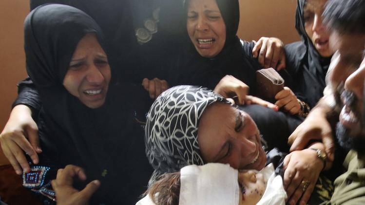 Relatives of al-Araj mourn over his body during his funeral in Khan Younis in the southern Gaza Strip