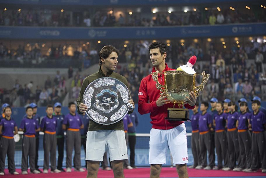China Open Tennis winner Novak Djokovic of Serbia, right, chats with Rafael Nadal of Spain as they pose with their trophies after the final of the China Open tennis tournament at the National Tennis Stadium in Beijing, China Sunday, Oct. 6, 2013. Djokovic defeated Nadal 6-3, 6-4