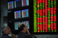 Investors look at stock prices at a securities brokerage in Shanghai. Asian shares were mixed as lingering hopes for the global economy were offset by profit-taking after last week's healthy gains, while heavy losses on Wall Street added to selling pressure