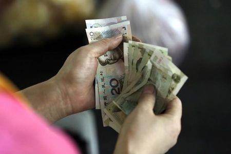 A customer counts Chinese Yuan notes at a market in Beijing