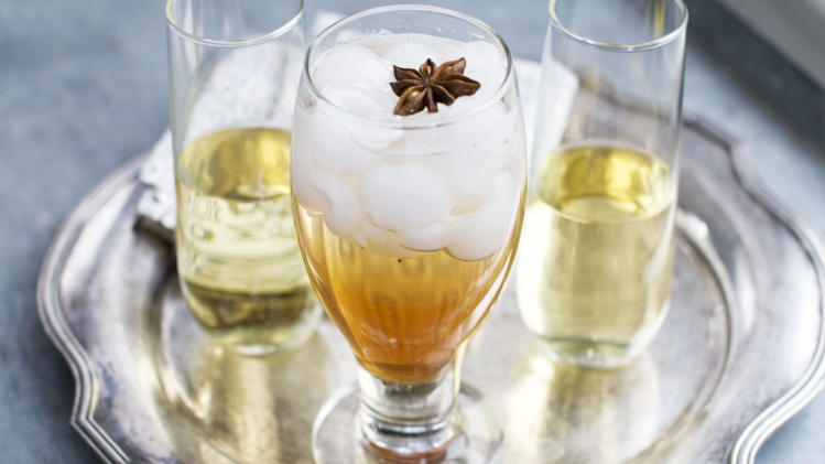 In this image taken on Jan. 28, 2013, a glass of spiced-rose pomegranate spritzer with a star anise on top, center, and two glasses of sparkling wine are shown on a serving tray in Concord, N.H. (AP Photo/Matthew Mead)
