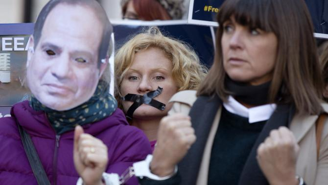 A protester has her mouth taped while demonstrating for the release of Al Jazeera journalists in London
