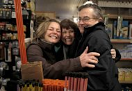 "In this photo taken Saturday, Jan. 21, 2012, shoppers and long time friends Cheryl Black, left, and Sherry Williams hug Jack Shutts at Chagrin Hardware in Chagrin Falls, Ohio. Black's husband Jim wrote an email to 40 friends asking them to pass the word along to ""Occupy CF Hardware"" on Saturday and spend at least $20.00 in support of the owners, the Shutts family. (AP Photo/Amy Sancetta)"