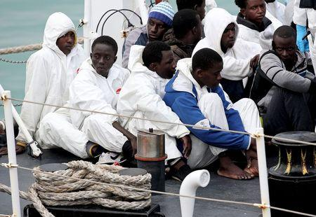 Migrants look on before arriving at the Sicilian harbor of Catania