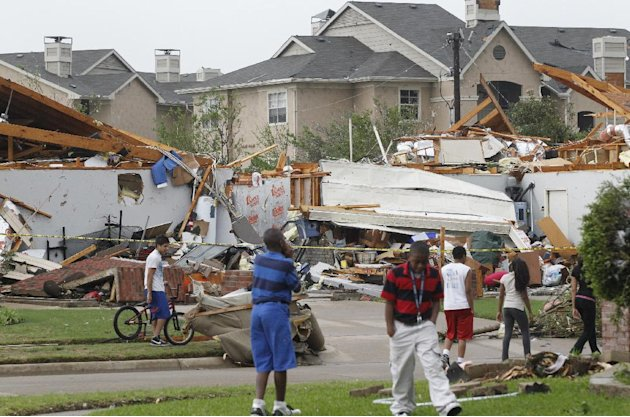 Neighbors view what remains of a home in Arlington, Texas, Tuesday April 3, 2012. Tornadoes tore through the Dallas area Tuesday, peeling roofs off homes, tossing big-rig trucks into the air and leavi
