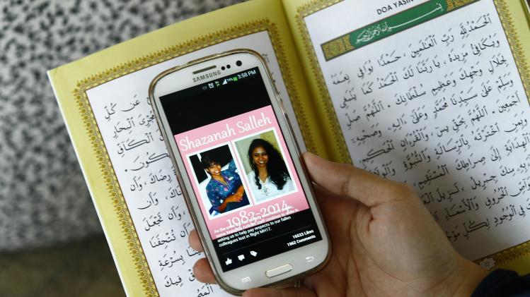Karim holds her mobile phone displaying a picture of Malaysia Airlines Flight MH17 flight attendant Salleh, during a special prayer at the Tuanku Mizan Zainal Abidin mosque in Putrajaya