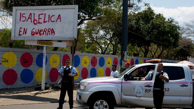 """In this photo taken on Saturday, March 15, 2014. Carabobo's State police officers stand next to graffiti that reads in Spanish """"Isabelica in war"""" during a opposition protest at Isabelica neighborhood outside Valencia , Venezuela. The people of the poor district of La Isabelica were made to pay for taking to the streets in anti-government protests. More than a dozen masked men on motorcycles roared through, shooting up a barricade and killing a university student and a 42-year-old man painting his house. (AP Photo/Fernando Llano)"""