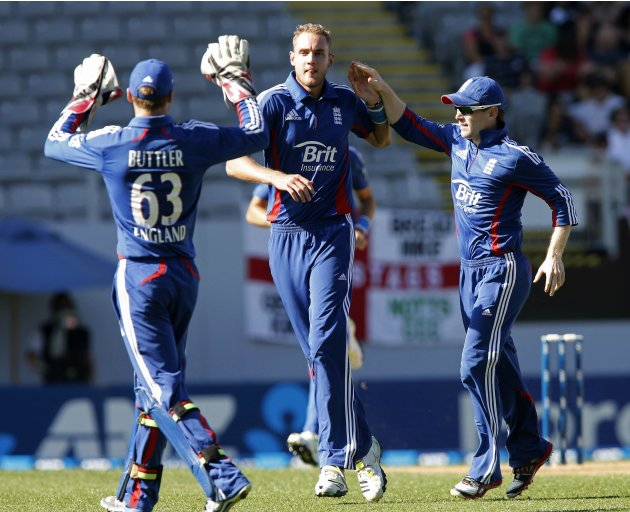 Broad of England is congratulated by teammates Buttler and Bell after dismissing Ellis of New Zealand during the final cricket match of their one day international series at Eden Park, Auckland