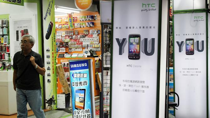 In this photo taken Thursday, Oct. 25, 2012, a man walks by advertising boards of HTC Corp., two at right, and Samsung Electric Co., in Taipei. Taiwan's top smartphone maker HTC is trying hard to halt its sliding sales and keep its status as a strong global brand in a market increasingly dominated by Apple Inc. and Samsung Electronics Co. is trying hard to halt its sliding sales and keep its status as a strong global brand in a market increasingly dominated by Apple Inc. and Samsung. (AP Photo/Chiang Ying-ying)