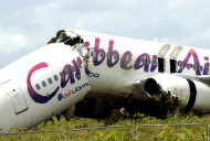 The broken fuselage of a Caribbean Airlines' Boeing 737-800 is seen after it crashed at the end of the runway at Cheddi Jagan International Airport in Timehri, Guyana, Saturday, July 30, 2011. The Caribbean Airlines flight 523 from New York touched down on the rainy runway, slid through a chain-link fence and broke apart just short of a ravine but there were no immediate reports of death among the 163 people aboard, despite several dozen of injuries. (AP Photo/Jules Gibson)