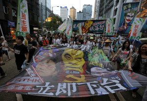 Protesters carry a banner featuring with Hong Kong's …