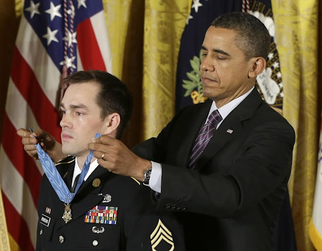 President Barack Obama bestows the Medal of Honor on retired Staff Sgt. Clinton Romesha for conspicuous gallantry, Monday, Feb. 11, 2013,  in the East Room of the White House in Washington. Romesha's 
