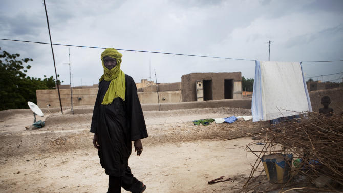 In this Thursday, Sept. 27, 2012 photo, former Timbuktu souvenir vendor Mamadou Sekere walks at the home where part of his family has taken refuge in Mopti, Mali. Before Islamists seized the northern half of Mali, Sekere sold masks and jewelry in Timbuktu to European tourists who rode camels and slept in the desert under the stars. Ordinary Malians and international experts alike are not sure what will reunite and bring back political stability to a country that until recently had a reputation as one of West Africa's most steady democracies. Representatives of the United Nations, the African Union and regional body ECOWAS are to consider the situation on Oct. 19, 2012 in a meeting in Mali's capital, Bamako. (AP Photo)