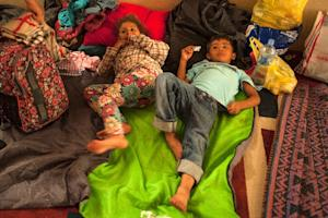Two migrant children prepare to sleep in a Macedonian…