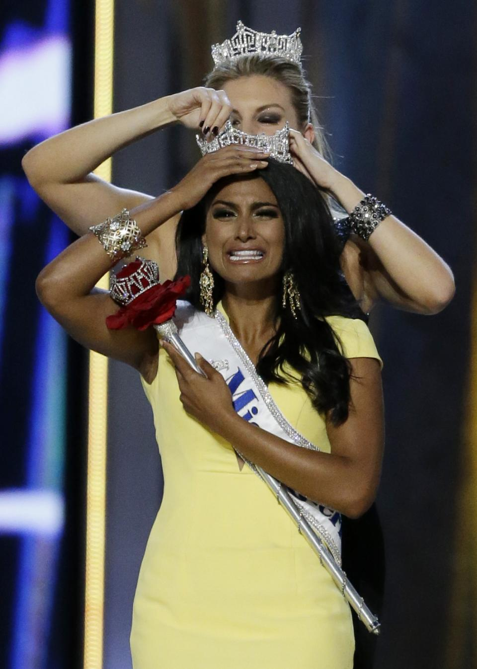 Miss New York Nina Davuluri, front, is crowned as Miss America 2014 by Miss America 2013 Mallory Hagan, Sunday, Sept. 15, 2013, in Atlantic City, N.J. (AP Photo/Julio Cortez)