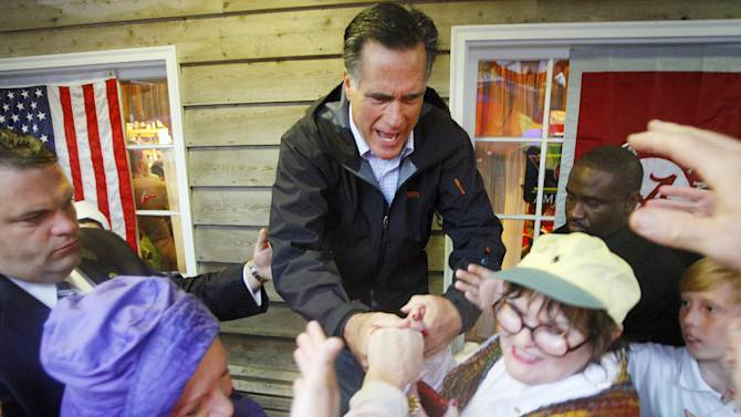 Republican presidential candidate, former Massachusetts Gov. Mitt Romney greets supporters who braved the rain during a campaign stop at the Whistle Stop Cafe, Monday, March 12, 2012 in Mobile, Ala. (AP Photo/ John David Mercer)