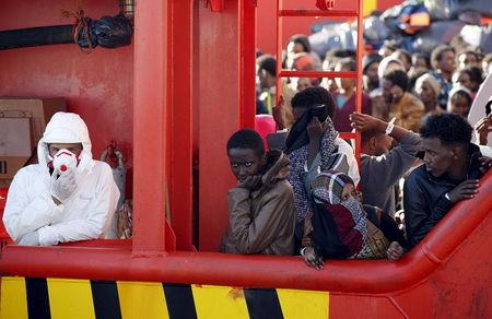 Migrants wait to disembark from tug boat Asso29 in the Sicilian harbour of Pozzallo, southern Italy