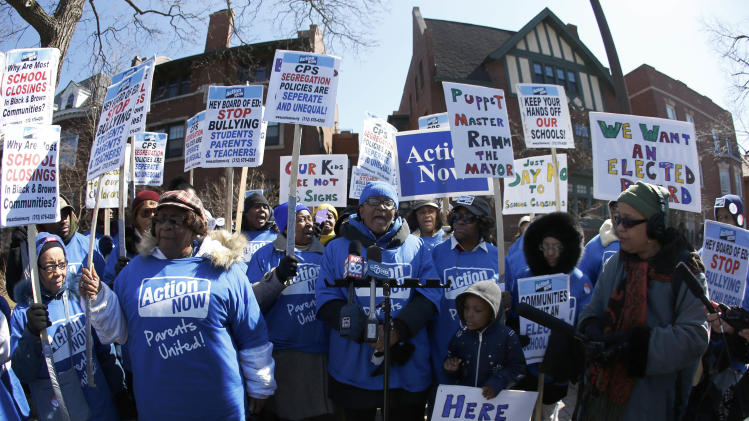 Parents protest outside the home of Chicago's Board of Education President David Vitale's house Thursday, March 21, 2013, in Chicago. Teachers say the city of Chicago has begun informing teachers, principals and local officials about which public schools it intends to close under a contentious plan that opponents say will disproportionately affect minority students in the nation's third largest school district. Chicago Public Schools hasn't said how many schools or students will be affected, but administrators identified up to 129 schools that could be shuttered, saying many serve too few students to justify remaining open. (AP Photo/Charles Rex Arbogast)