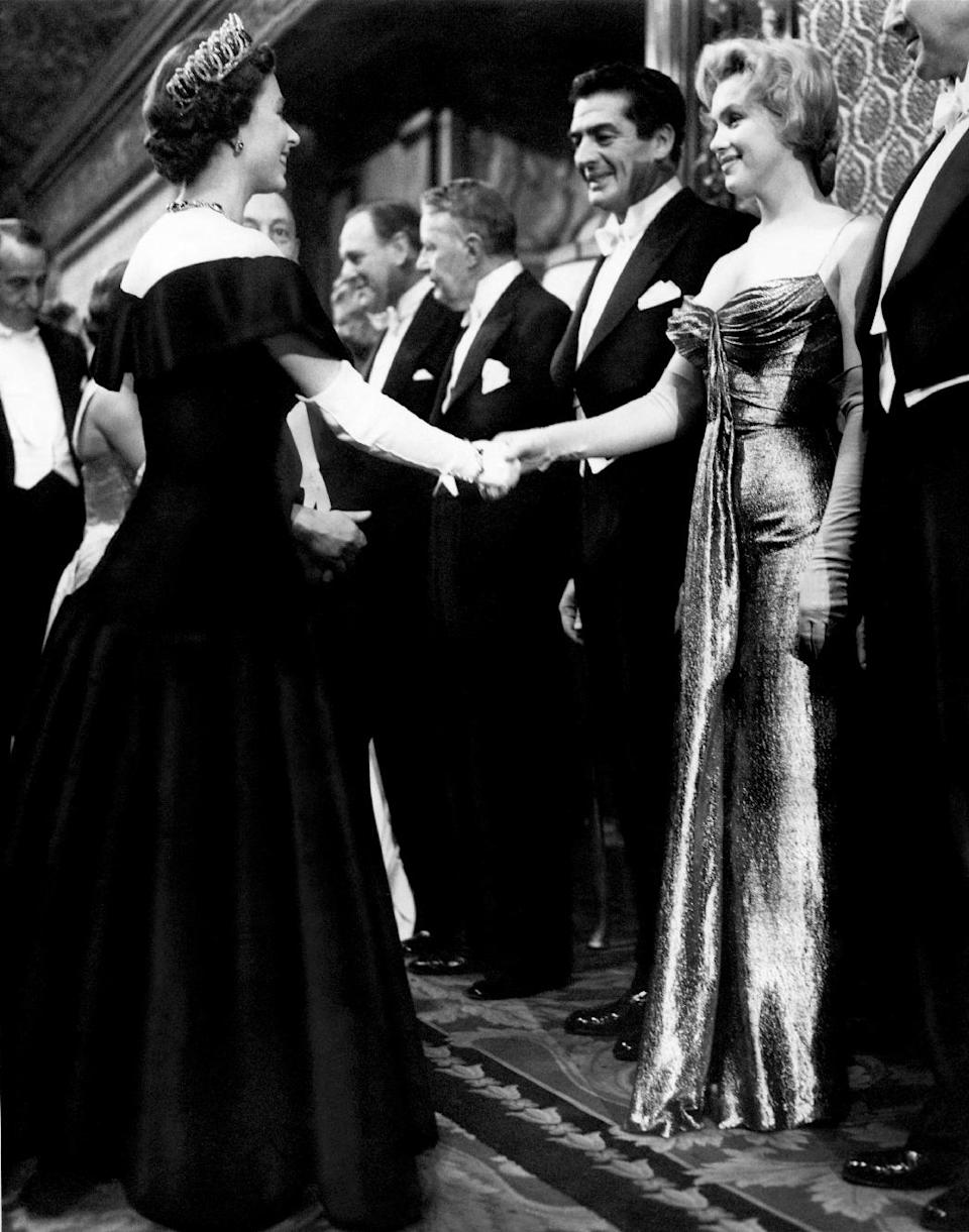 "In this late October 1956 photo provided by Running Press, Marilyn Monroe, right, wearing a burnished gold lamé gown meets the Queen in London. The photograph is included in a new 2012 book, ""Marilyn in Fashion,"" published by Running Press. (AP Photo/Courtesy Running Press)"