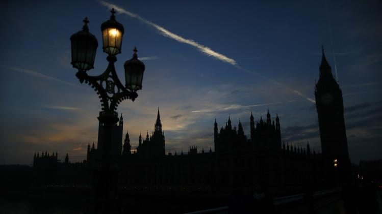 Street lights warm up on next to the Houses of Parliament at dusk in London