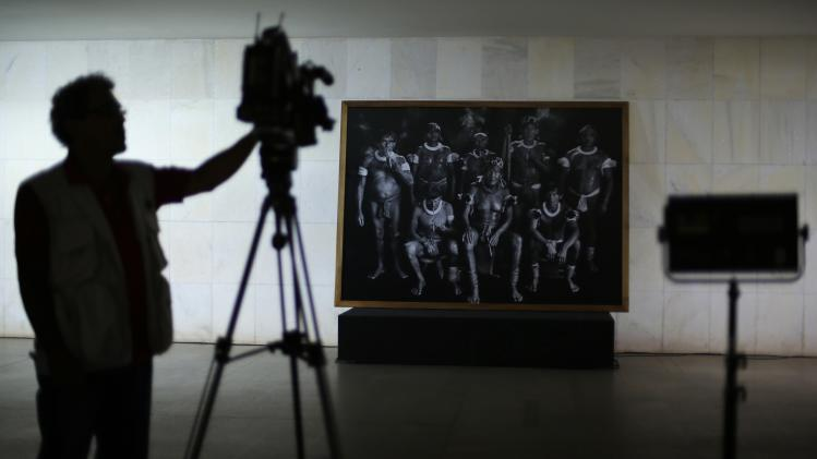 "A cameraman films Brazilian photographer Sebastiao Salgado during a donation ceremony of the photograph ""Shamans in Xingu"" to the Brazilian government, at the Itamaraty Palace in Brasilia"