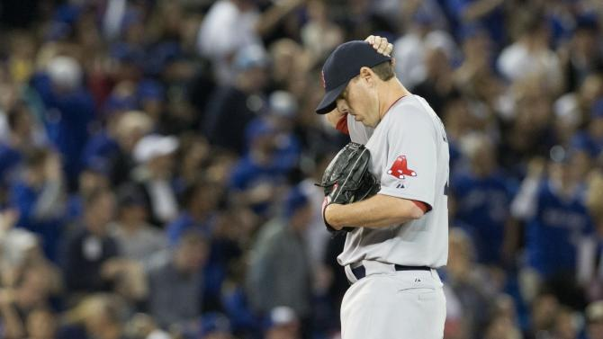 Boston Red Sox pitcher John Lackey reacts after giving up a two-run home run to Toronto Blue Jays' J.P. Arencibia during the fourth inning of a baseball game in Toronto on Saturday, April 6, 2013.(AP Photo/The Canadian Press, Chris Young)