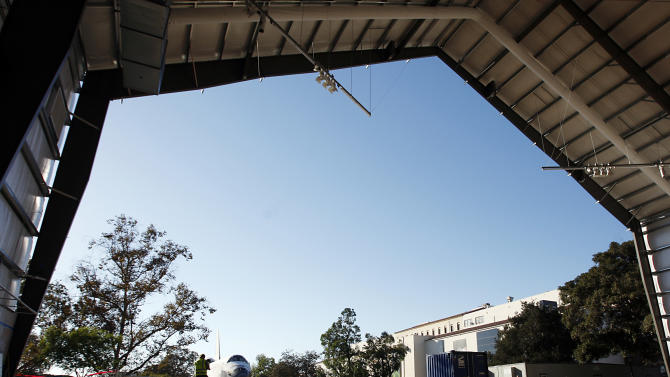 The space shuttle Endeavour sits outside its temporary hangar at the California Science Center in Los Angeles on Sunday, Oct. 14, 2012. After a 12-mile (19-kilometer) weave past trees and utility poles that included thousands of adoring onlookers, flashing cameras and even the filming of a TV commercial, Endeavour arrived at the California Science Center Sunday to a greeting party of city leaders and other dignitaries that had expected it many hours earlier. (AP Photo/Los Angeles Times, Luis Sinco, Pool)